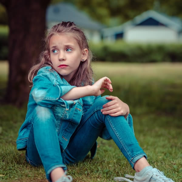 Girl Wearing Denim sitting on grass